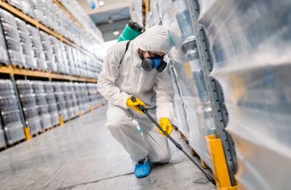 Exterminator in factory spraying pesticide with sprayer.